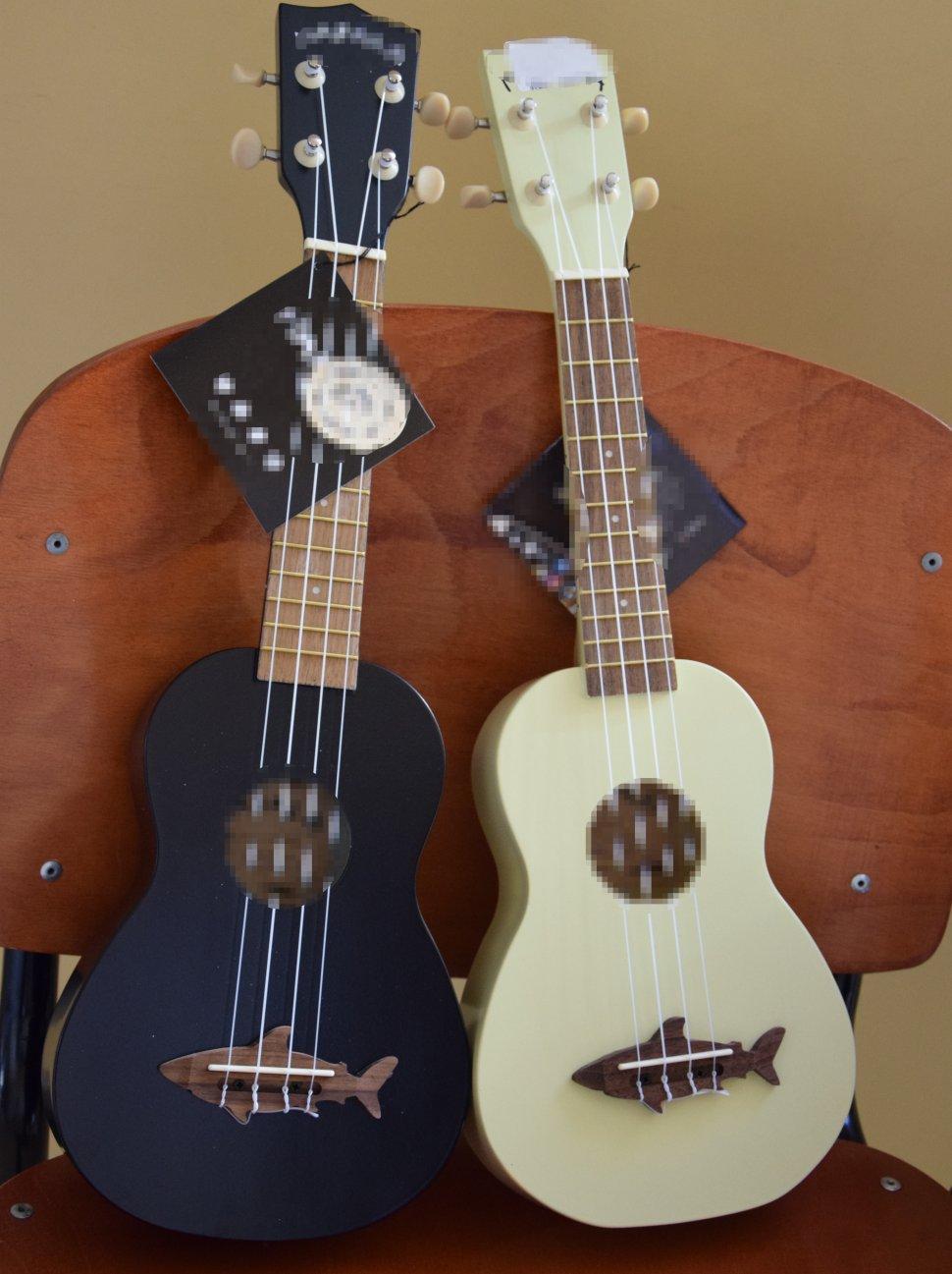 zdjęcie kolorowa: na zdjęciu widać 2 sztuki ukulele w kolorze czarnym i białym