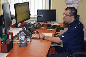 Na zdjęciu widać stanowisko pracy dyżurnego tarnogórskiej komendy. Policjant siedzi przy biurku i patrzy w monitor komputera. Na biurku widać telefony, radiostację oraz monitory komputerowe.